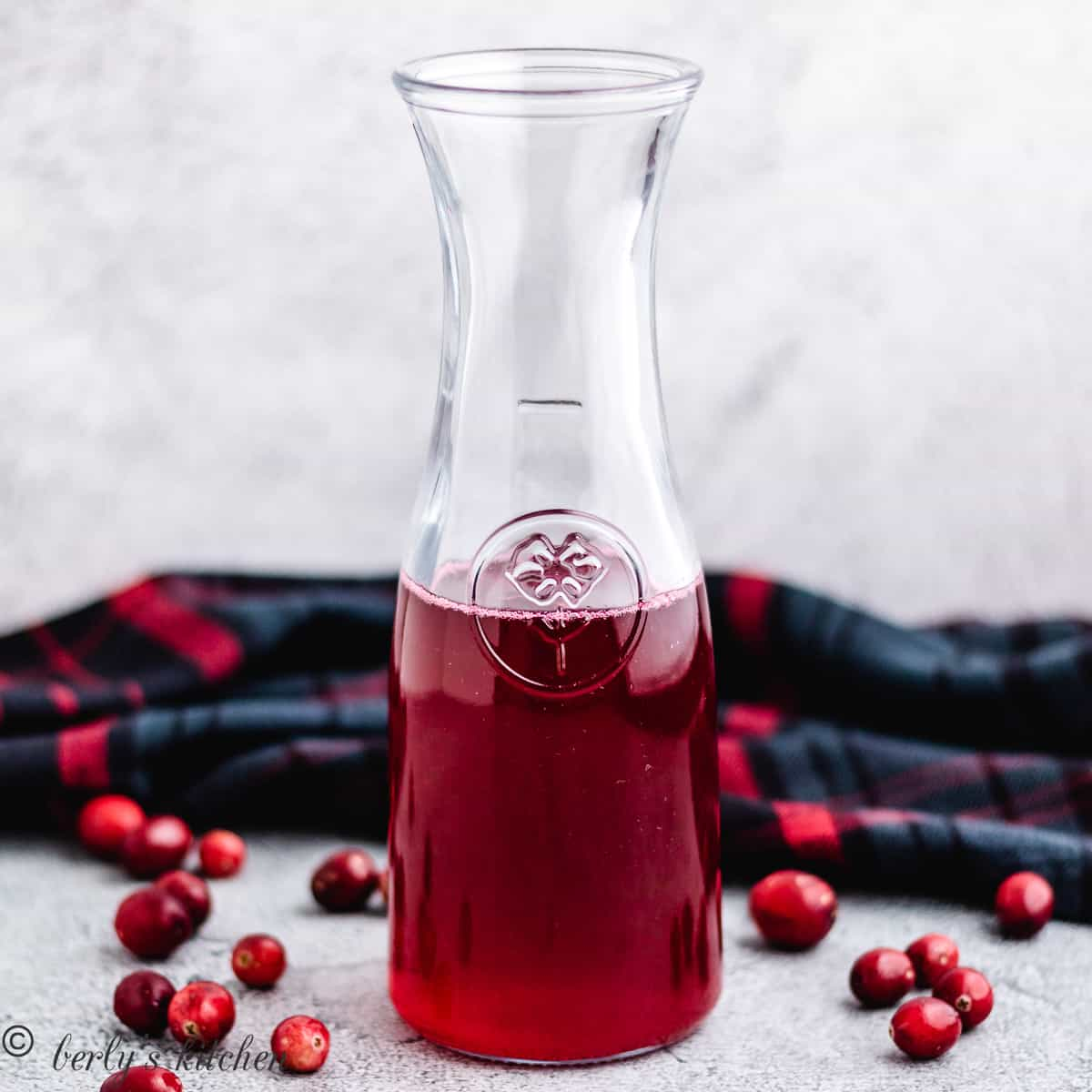 The tart cranberry syrup in a pitcher.