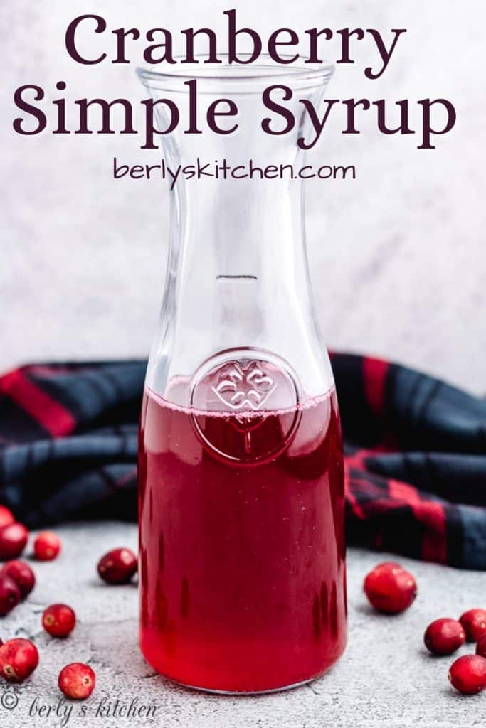Cranberry simple syrup in a pitcher surrounded by fresh cranberries.