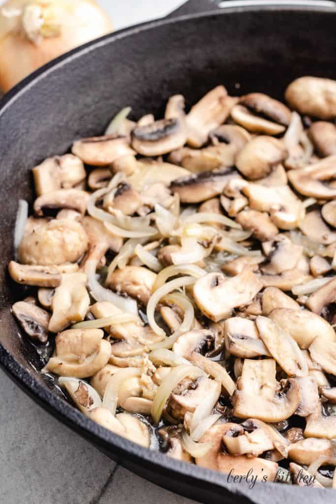 Sliced mushrooms and other ingredients cooking in a skillet.