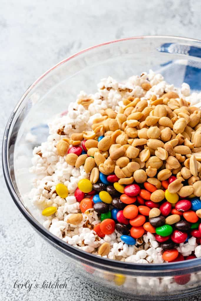 Peanuts, chocolate candies, and popcorn in a bowl.