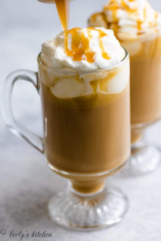 Butterscotch sauce being drizzled over whipped cream.