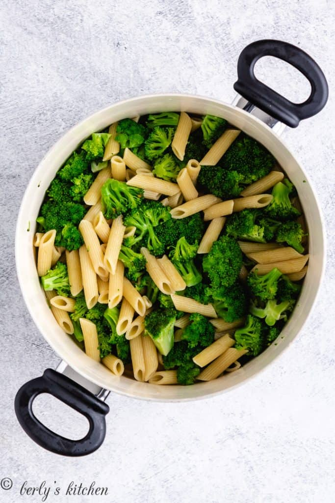 Penne noodles and broccoli florets cooked in a pot.