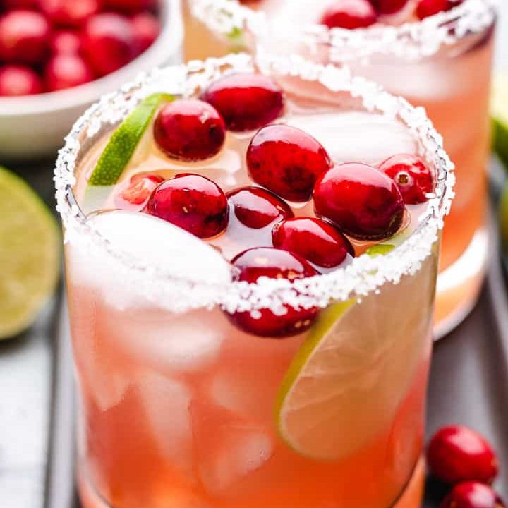 Cranberry margaritas in glasses garnished with fresh cranberries.