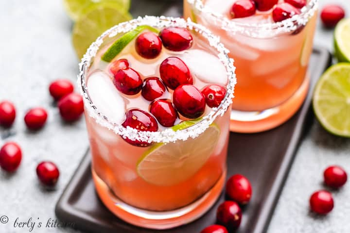 A top-down view of two cranberry margarita cocktails.