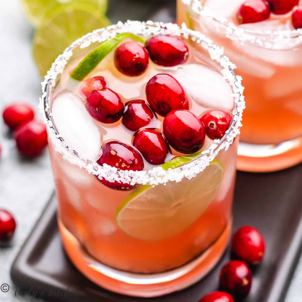 A cranberry margarita garnished with salt and fresh cranberries.