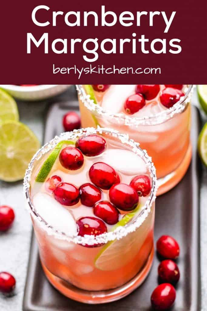 Two cranberry margaritas garnished with lime, cranberries, and salt.
