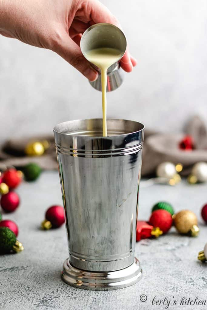 Eggnog being poured into a cocktail shaker.