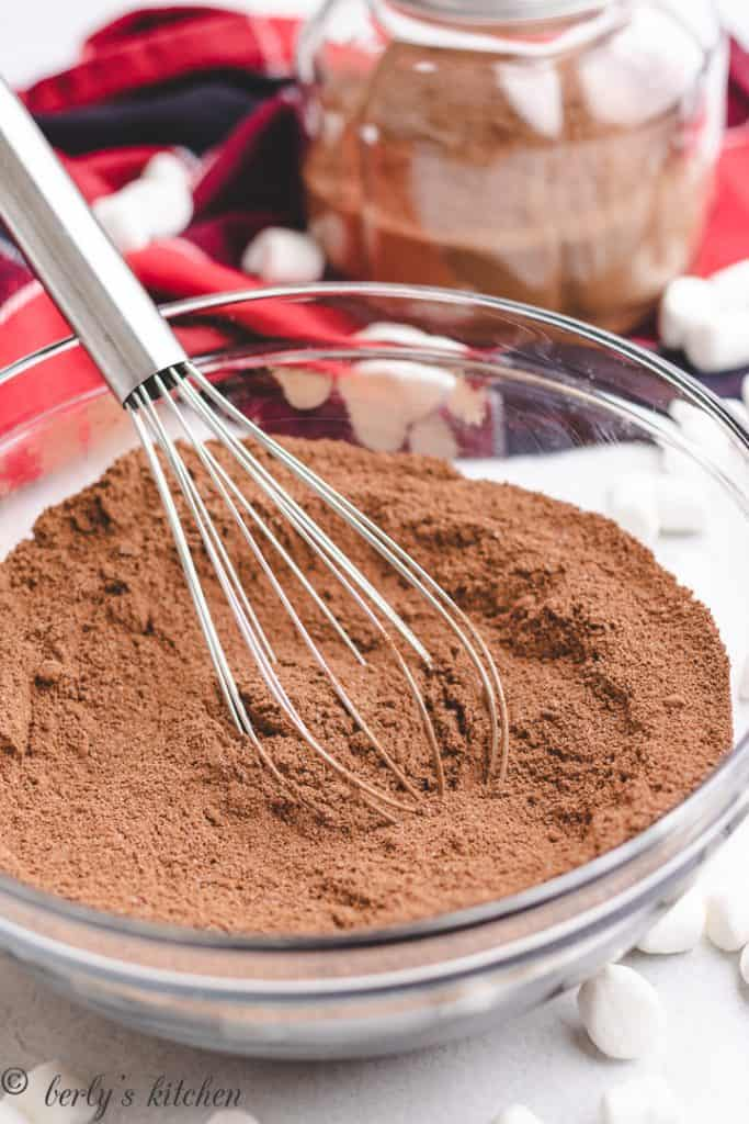 Ingredients for hot chocolate mix in a glass bowl.
