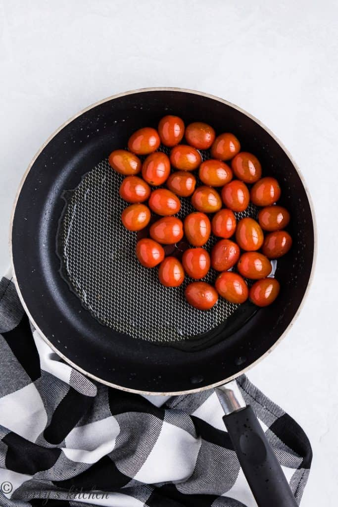 Cherry tomatoes cooking in a sauté pan.