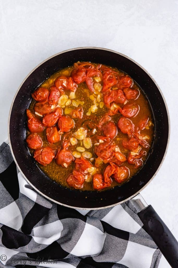 Tomatoes, garlic, and broth cooking in the pan.