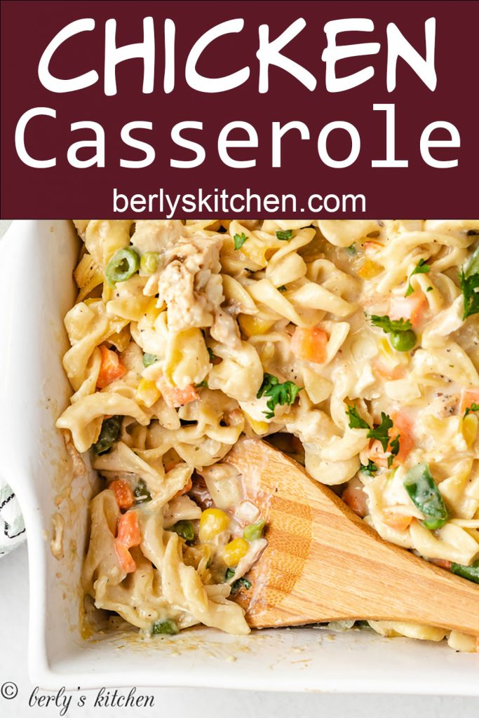 Close up of creamy chicken noodle casserole with a wooden spoon.