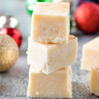 Three pieces of eggnog fudge stacked on each other.