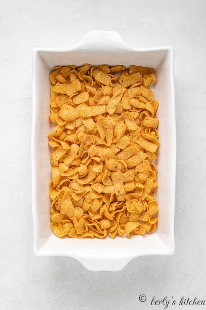 Corn chips layered into a baking dish.