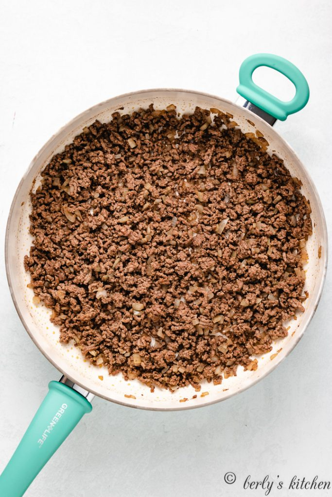 Ground beef and other ingredients cooked in a skillet.