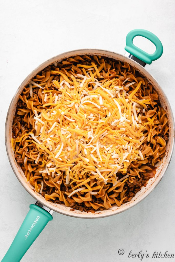 Shredded cheese added to the cooked noodles and beef.