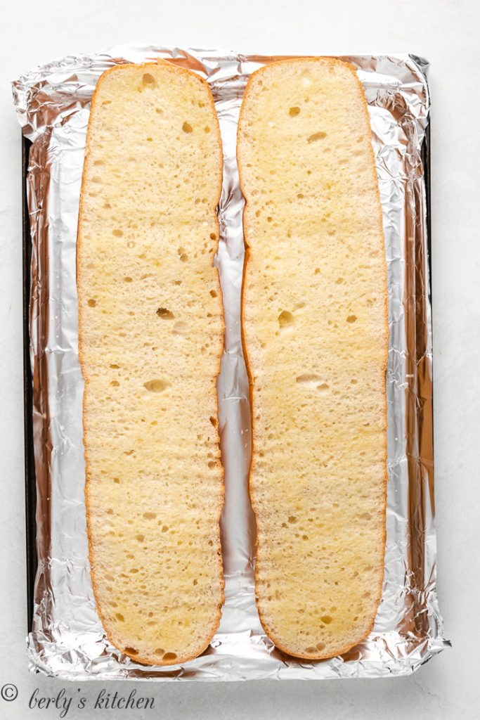 Sliced French bread on a baking sheet lined with aluminum foil.