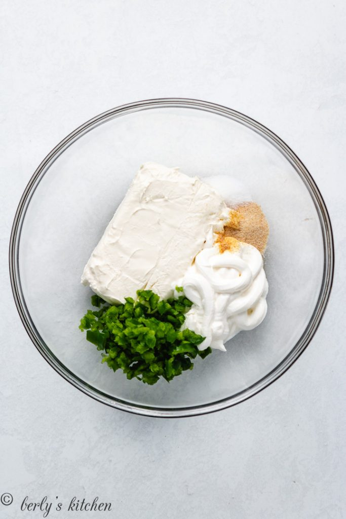 Cream cheese, sour cream, and other ingredients in a mixing bowl.