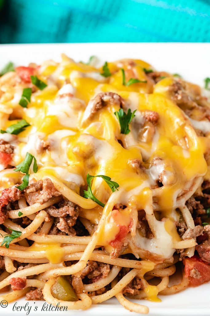 Close of cheesy spaghetti on a white dish.