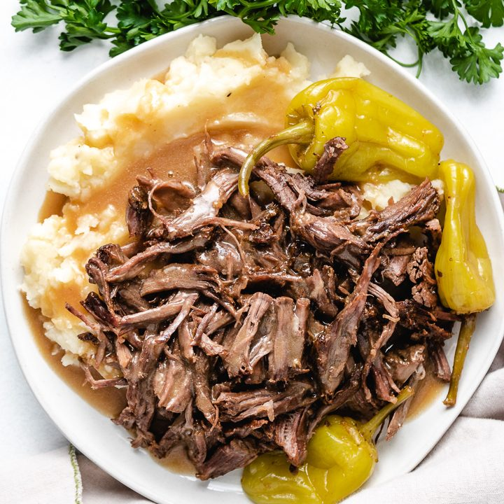 Pot roast and mashed potatoes with pepperoncinis.