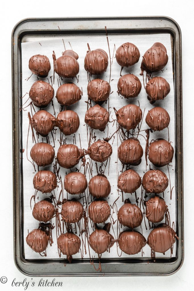 The dipped peanut butter balls placed on a lined baking sheet.