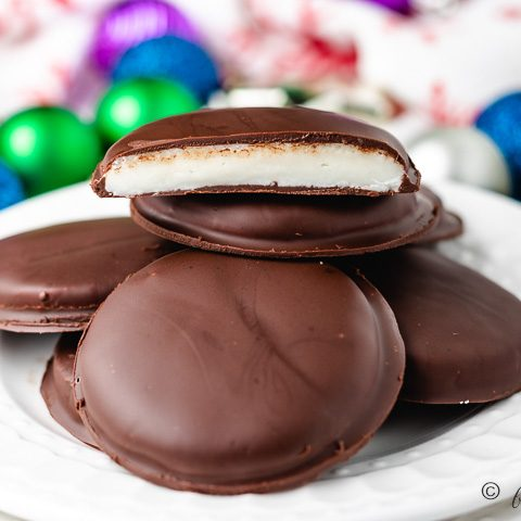 A pile of peppermint patties on a white plate.