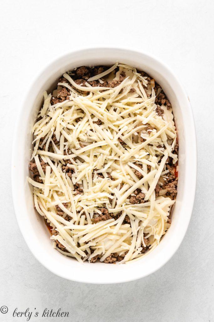 Marinara, raviolis, and cheese layered in a baking dish.