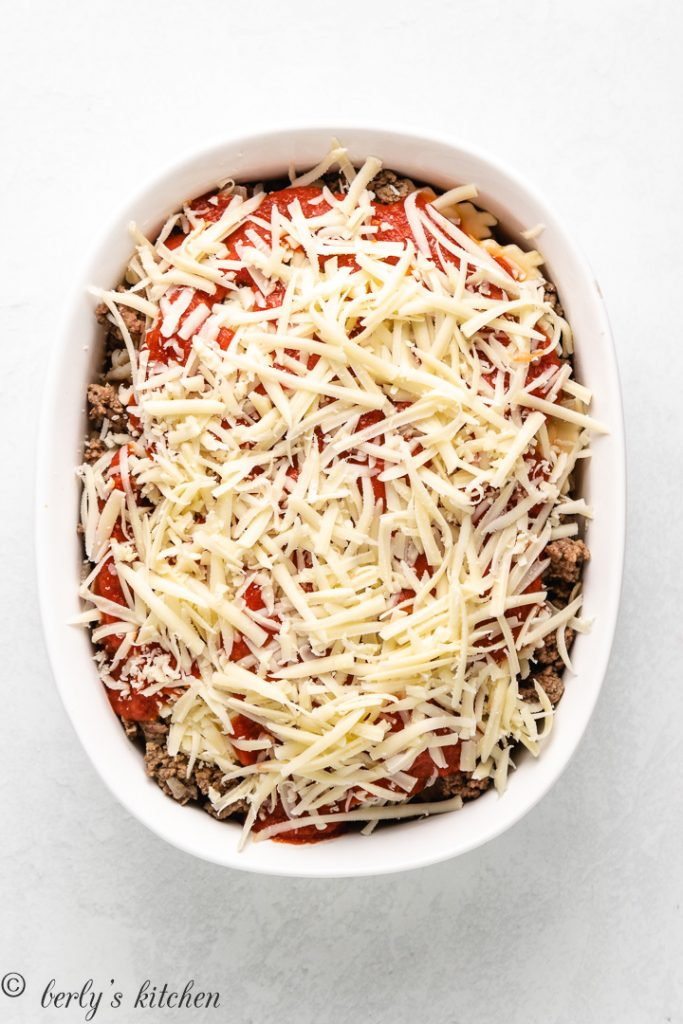 The uncooked lasagna topped with sauce and cheese.