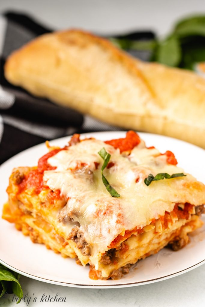 A slice of lasagna served with bread.