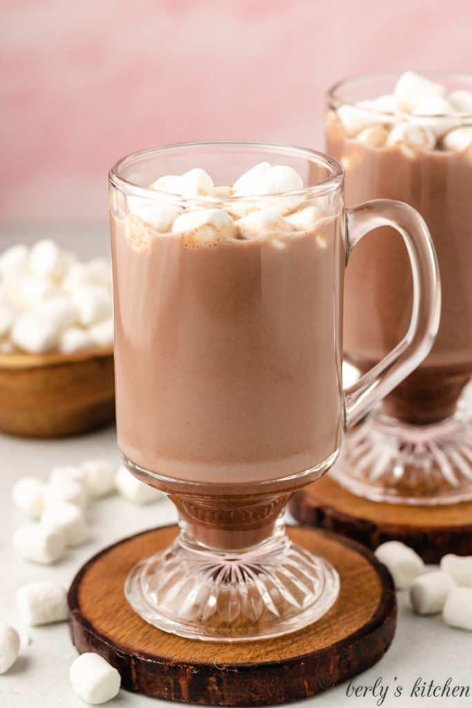 A glass mug filled with the hot cocoa.