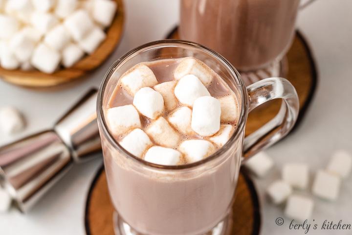 A rumchata hot chocolate served in a glass mug.