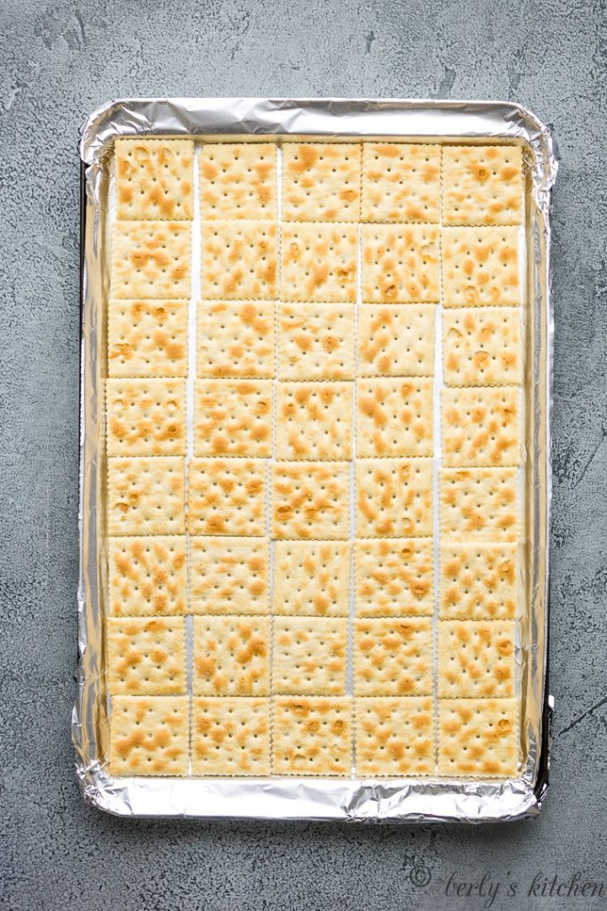 Soda crackers placed in a lined sheet pan.