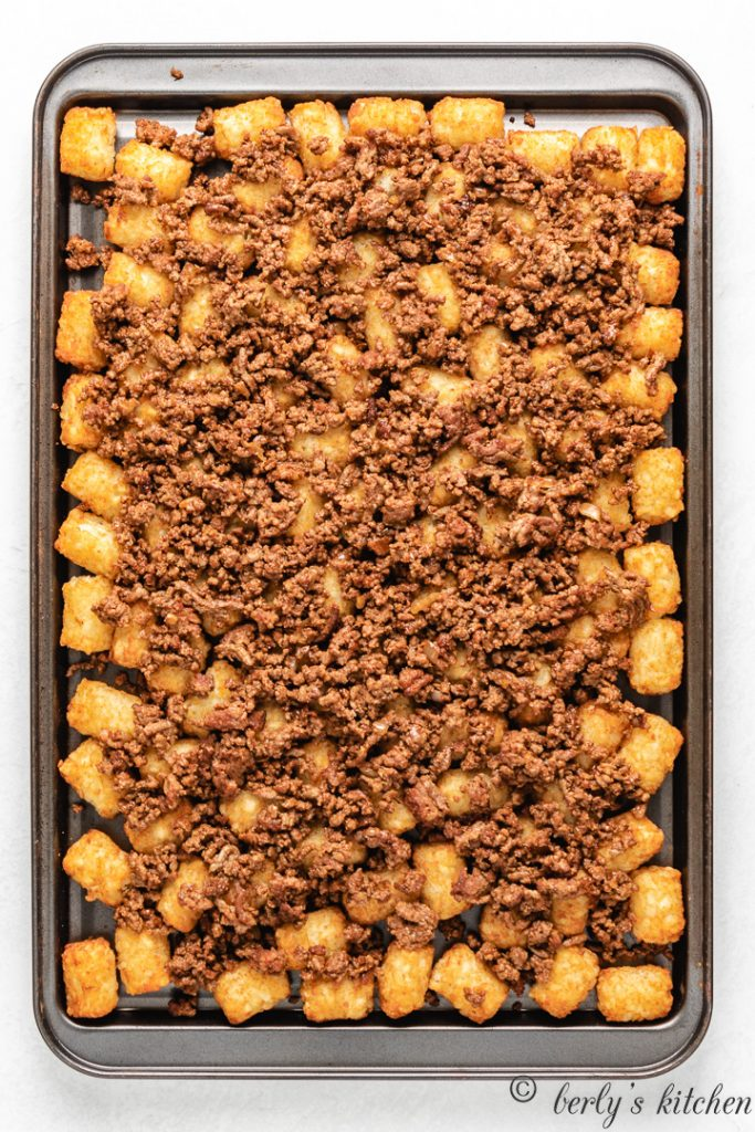 Top down view of ground beef on tater tots.