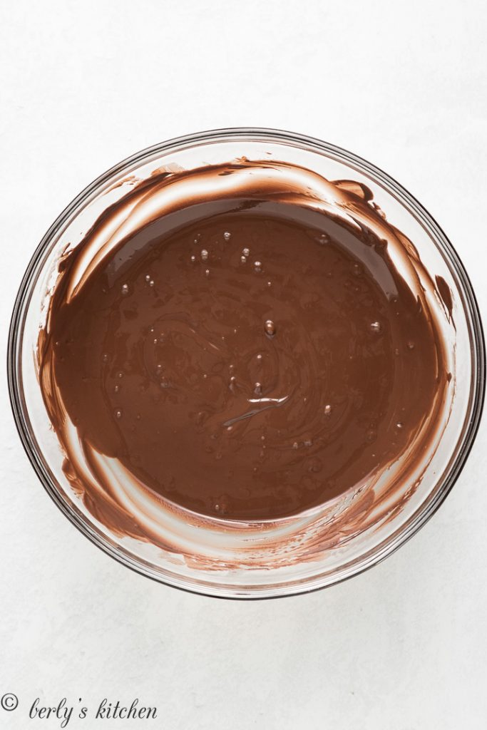 Melted chocolate in a glass mixing bowl.