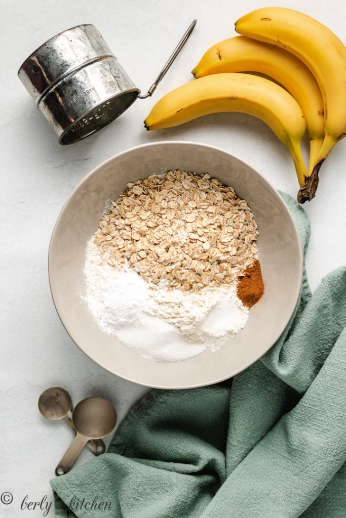 Oats, flour, and spices for pancakes in a gray bowl.