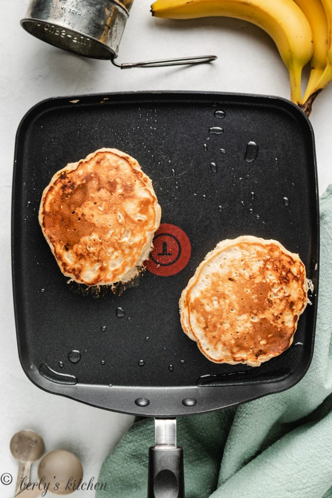 Two pancakes on a griddle.