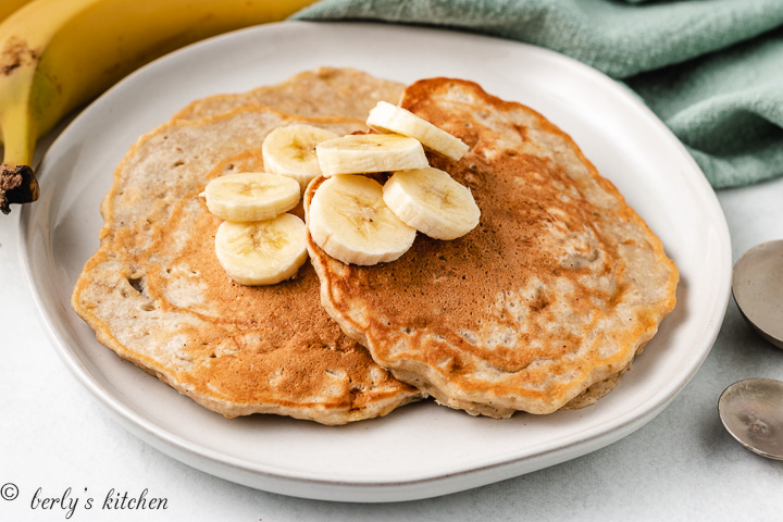 Banana oat pancakes on a plate with fresh banana slices.