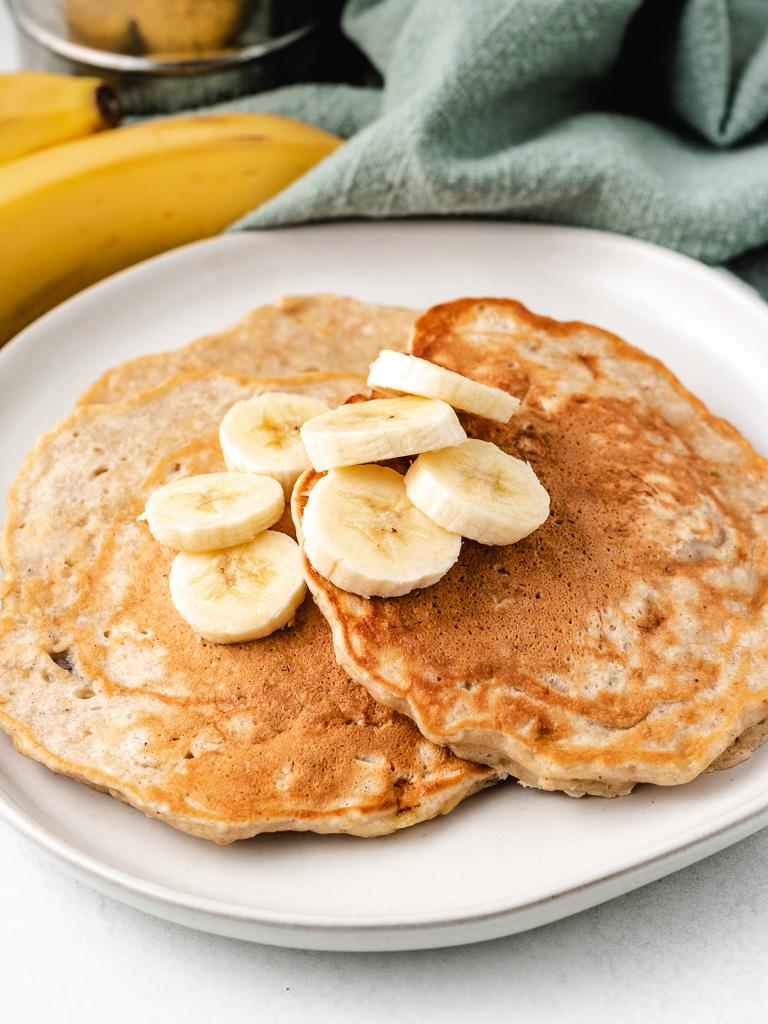 Pile of pancakes with fresh bananas on a plate.