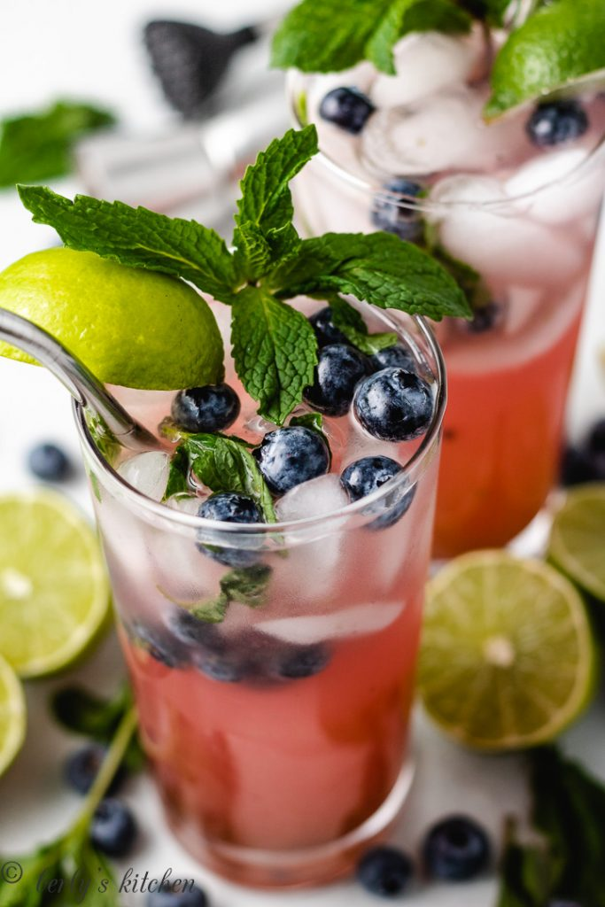 Two blueberry mojitos garnished with fresh berries and mint.