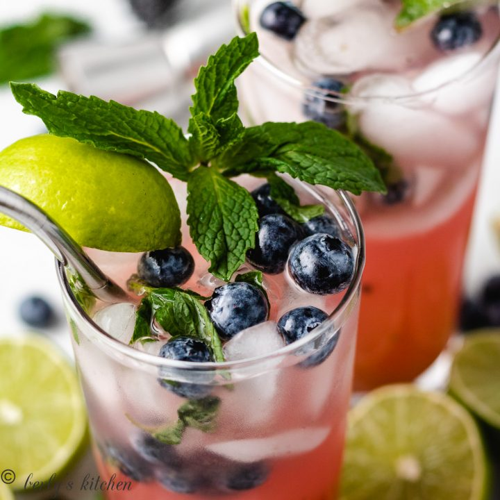 Two glasses of Blueberry Mojitos with fresh lime.
