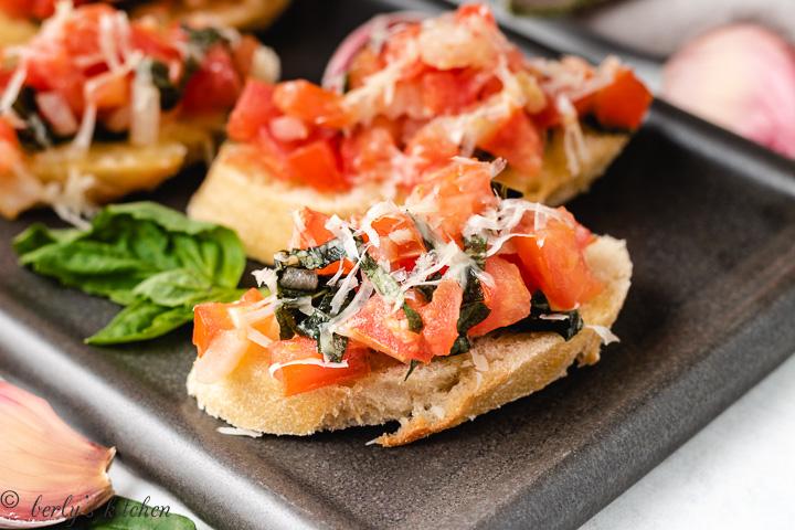 Basil and tomato bruschetta on sliced bread.