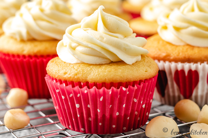 Close up of a yellow cupcake with white chocolate frosting.