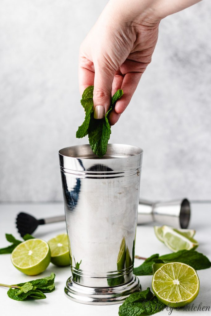 Fresh mint leaves being added to a metal shaker.