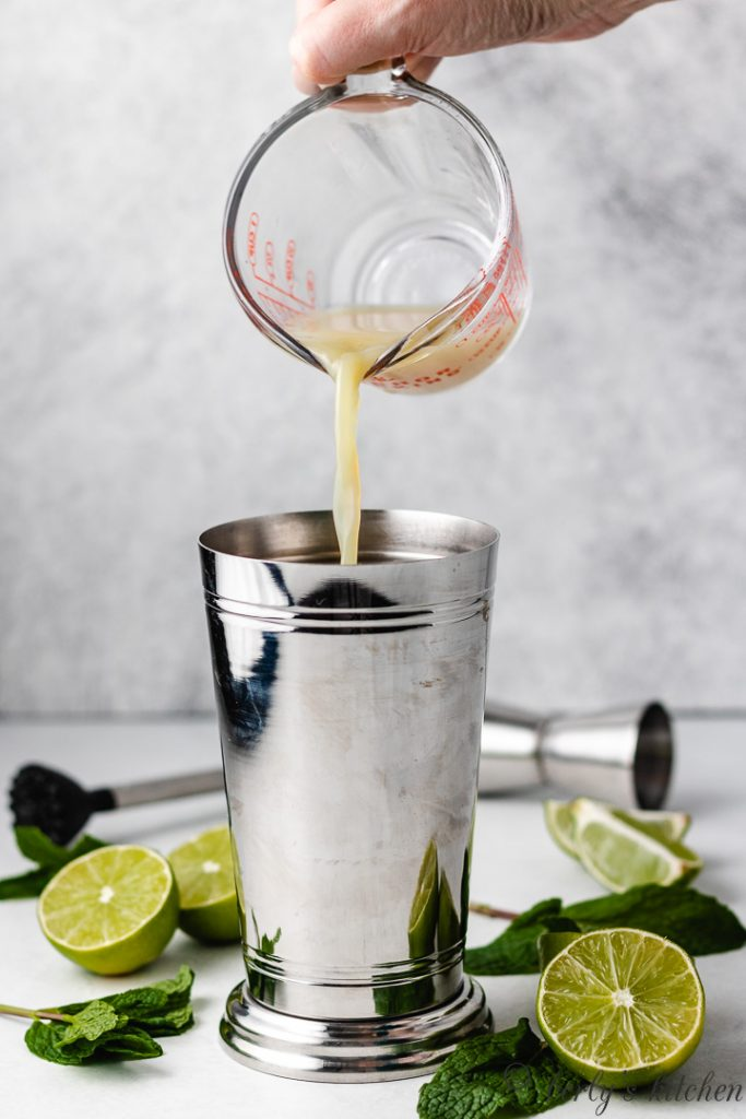 A measuring cup pouring lime juice into the shaker.