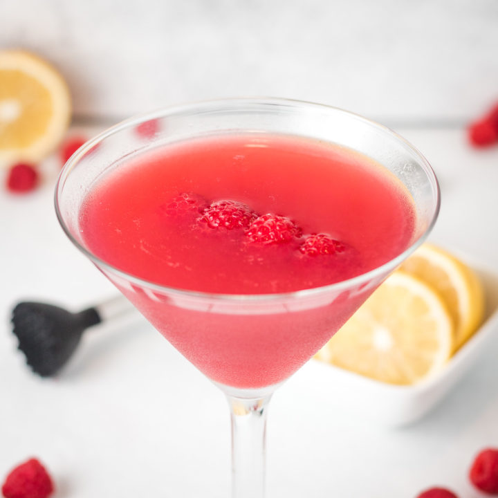 Raspberry Martini with fresh raspberries and lemon.