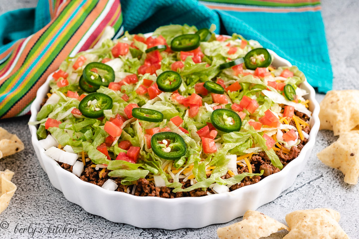 Taco dip in a white dish with taco toppings.