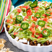 Taco dip with fresh tomatoes, cheese, and lettuce.