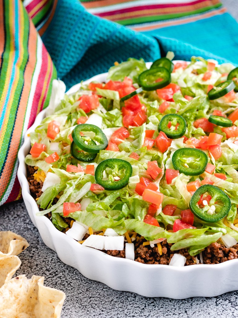Taco dip in a white serving dish.