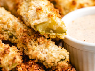 Air fried pickles on a plate with dressing.
