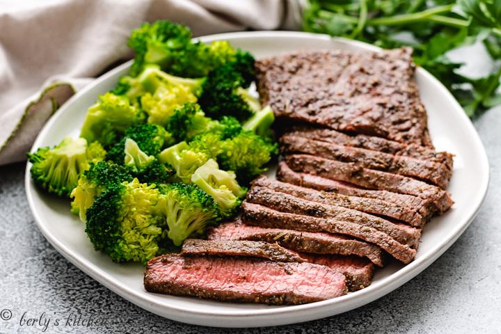 Seasoned steak with fresh steamed vegetables on a white plate.