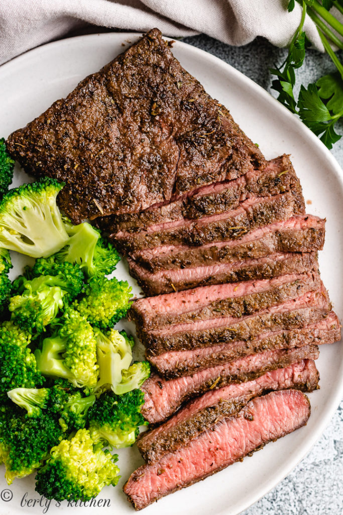 Cooked steak and steamed broccoli on a gray dish.